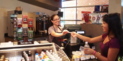A student hands her id card to the cashier at Biscotti's coffee shop at Penn State Harrisburg.