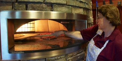 A food service employee puts a pizza in the brick pizza oven at Stack's Market at Penn State Harrisburg.